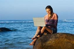 Project Manage Your Life - Confident woman working by the ocean,